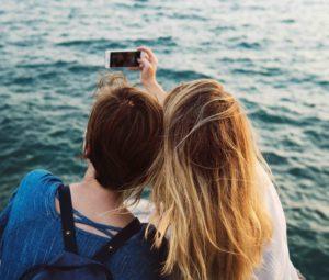 海でスマホを使って写真を撮ろうとする女性2人